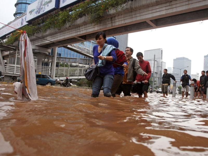 People wade through a flooded street in Jakarta, Indonesia. AP