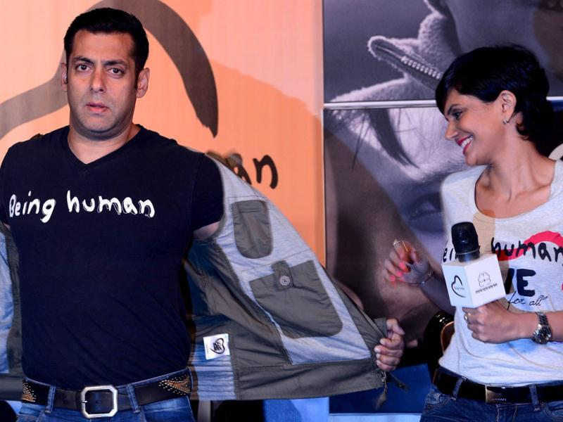 Mandira Bedia (R) looks on as Bollywood film actor Salman Khan takes off his jacket during the launch of his Being Human flagship clothing store in Mumbai on January 17, 2013. Khan announced the pan-India launch of his flagship retail store for 'Being Human' fashion apparel after having already launched in Paris, Belgium, Spain and Dubai. (AFP PHOTO)