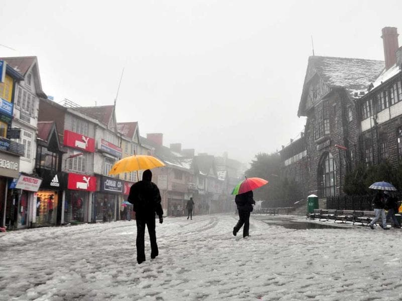 People walk through a snow covered road at Mall road, in Shimla. HT/Santosh Rawat