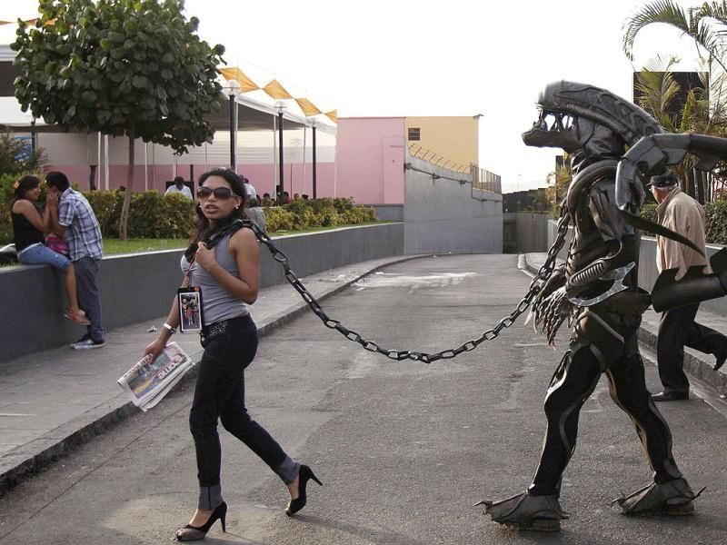 A woman pulls a chain attached to a man, wearing an alien monster costume, as the city of Lima marks the 478th anniversary of its Spanish founding in Lima. Reuters