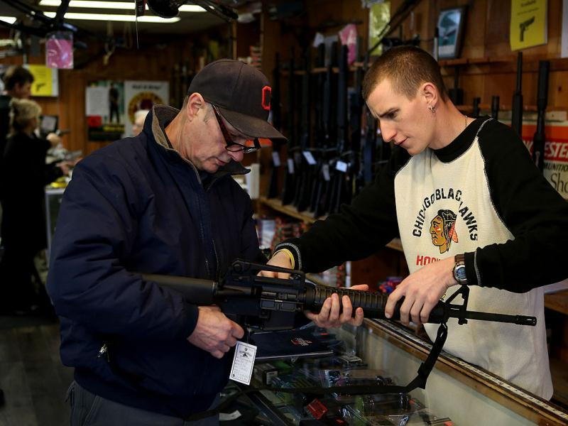 Anthony Santor (R) helps a customer select a rifle at Freddie Bear Sports sporting goods store in Tinley Park, Illinois. Gun rights supporters have proclaimed today Gun Appreciation Day and encouraged gun owners to visit local gun shops, gun ranges and to rally at their state capitals. (AFP Photo)