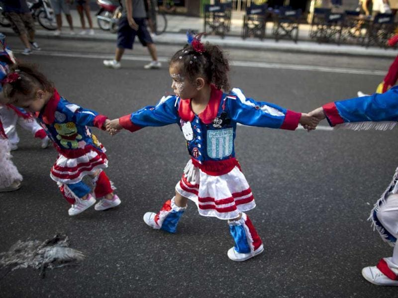Children, members of a murga, groups of extravagantly dressed dancers and drummers that parade their way through the streets, parade ahead carnival celebrations along Corrientes Avenue in Buenos Aires, Argentina. AP Photo