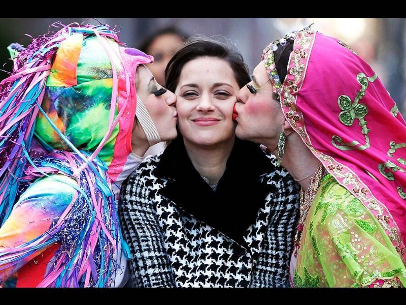 French actress Marion Cotillard, the Hasty Pudding Woman of the Year, is kissed by Harvard University theatrical students Renee Rober and Ben Moss as they ride in the back of a convertible during a parade through Harvard Square, in Cambridge. AP/Steven Senne