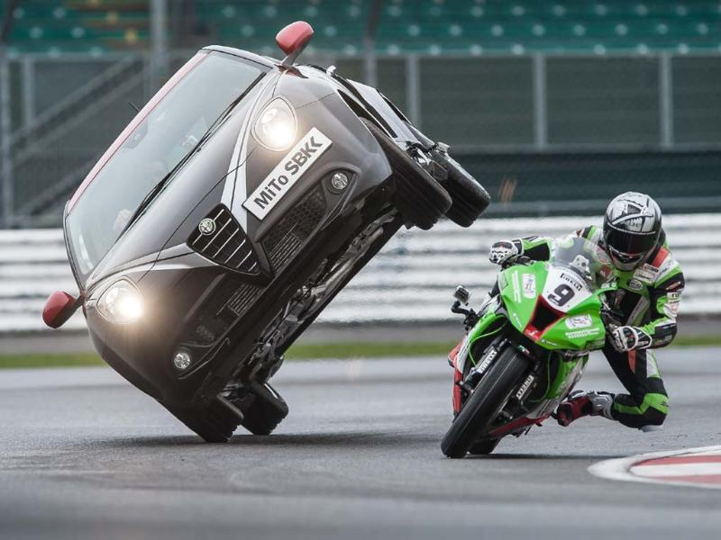 As the bike gets closer, Paul Swift balances the car on two wheels and Walker powers under on his Kawasaki. Photo:AFP