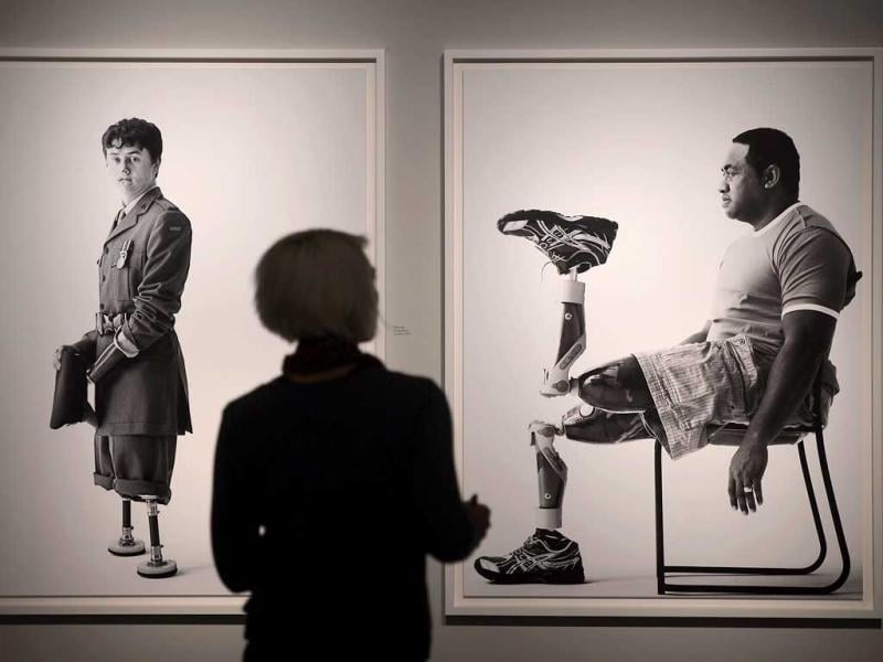 A visitor watches pictures of British war veterans photographed by Bryan Adams during the opening of his exhibition in Duesseldorf, Germany. AP