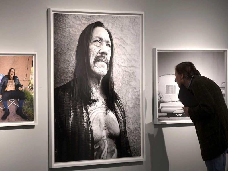 A visitor watches a picture of actor Danny Trejo, photographed by Bryan Adams during the opening of his exhibition in Duesseldorf, Germany. AP