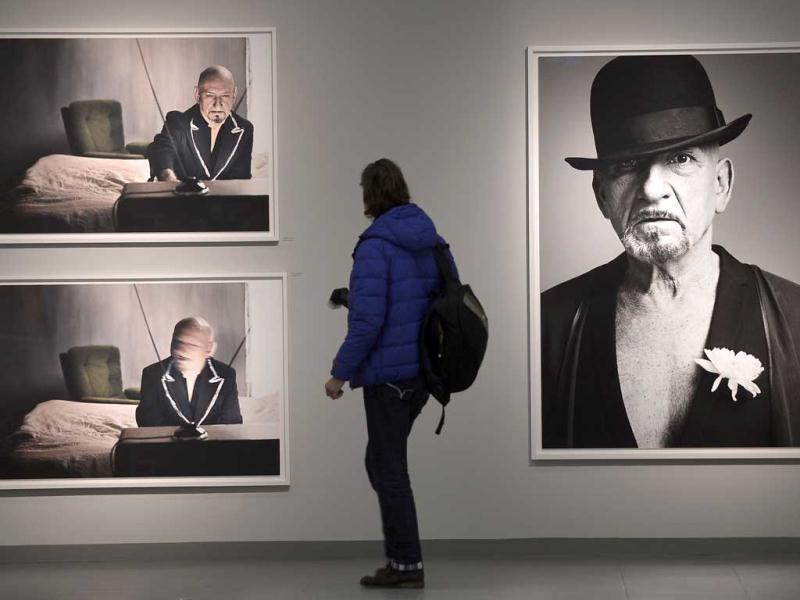 A visitor watches pictures of actor Ben Kingsley photographed by Canadian rock star Bryan Adams during the opening of his exhibition in Duesseldorf, Germany. AP