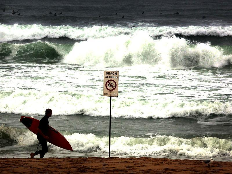 Surfers wait atop their boards as another runs past a sign on Manly Beach in Sydney. Rough seas and high winds have caused the closure of many Sydney beaches over the past few days. Reuters/David Gray