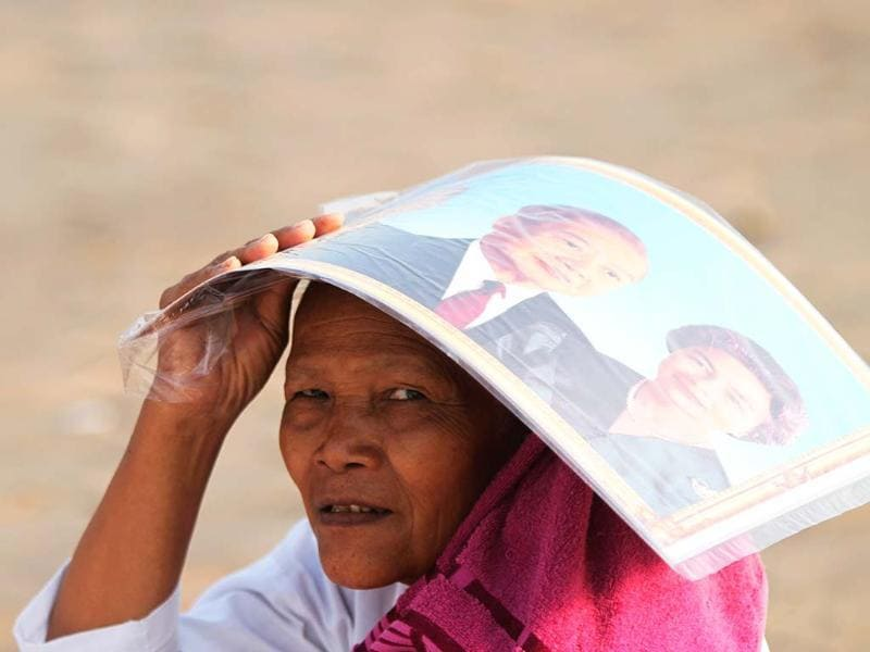 A mourner carries a portrait of Cambodia's late King Norodom Sihanouk and his wife Norodom Monineath Sihanouk on her head as she prays in front of the Royal Palace near a crematorium, where a coffin with the remains of King Sihanouk has been placed, in Phnom Penh. REUTERS