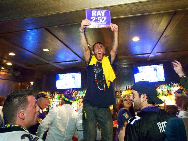 Joey Palmer, of Cincinnati (C) holds a placard celebrating Ray Lewis at the Famous Door Bar as fans celebrate the Baltimore Ravens defeating the San Francisco 49ers while fans from both NFL football teams pack the French Quarter on Bourbon Street for Super Bowl XLVII in New Orleans. (AP Photo)