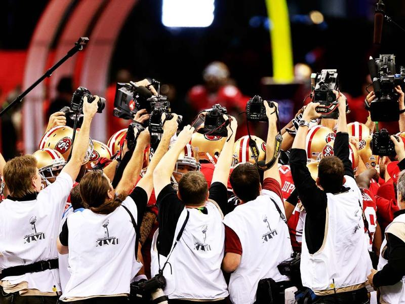 Photographers take pictures of members of the San Francisco 49ers huddling up prior to the start of Super Bowl XLVII against the Baltimore Ravens at the Mercedes-Benz Superdome in New Orleans, Louisiana.(AFP Photo)