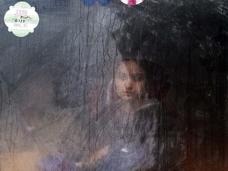 A commuter looks out from a bus window while travelling during a heavy downpour in New Delhi. Heavy rains lashed the capital bringing down the mercury and throwing normal life out of gear. AFP/Manan Vatsyayana