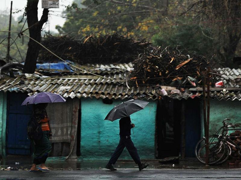 A schoolboy walks with an umbrella during a heavy downpour in New Delhi. AFP/Manan Vatsyayana
