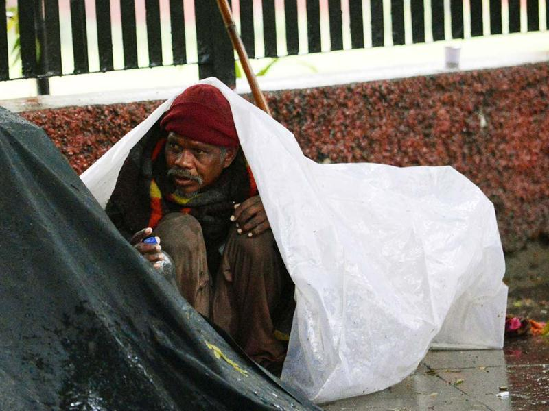 A homeless man takes shelter under a tarp as rain falls in New Delhi. AFP/Manan Vatsyayana