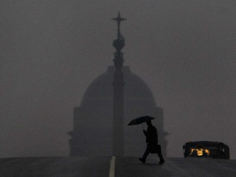 A man crosses a road at Raisina Hills as it rains in New Delhi. PTI/Vijay Verma