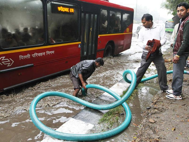 A municipal worker unclog drains near a bus stop in New Delhi. HT/Arvind Yadav