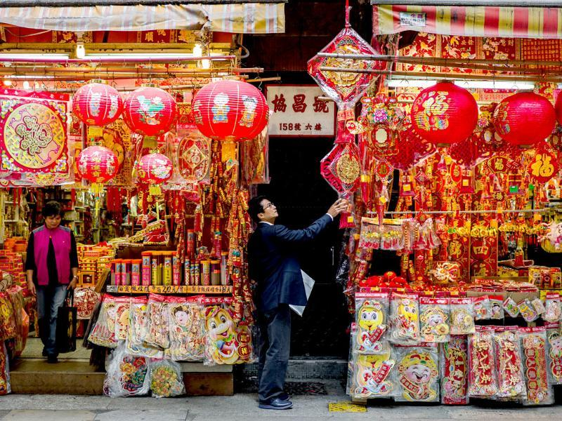 A man takes a look at a display of Chinese New Year decorations in Hong Kong. AFP/Philippe Lopez
