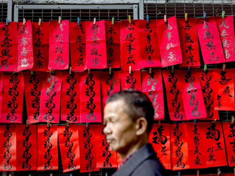 A man walks past Chinese New Year's calligraphy on red paper displayed in a street of Hong Kong. AFP/Philippe Lopez