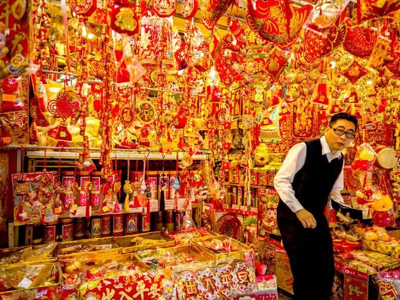 A man exits a shop selling Chinese New Year decorations in Hong Kong. AFP/Philippe Lopez