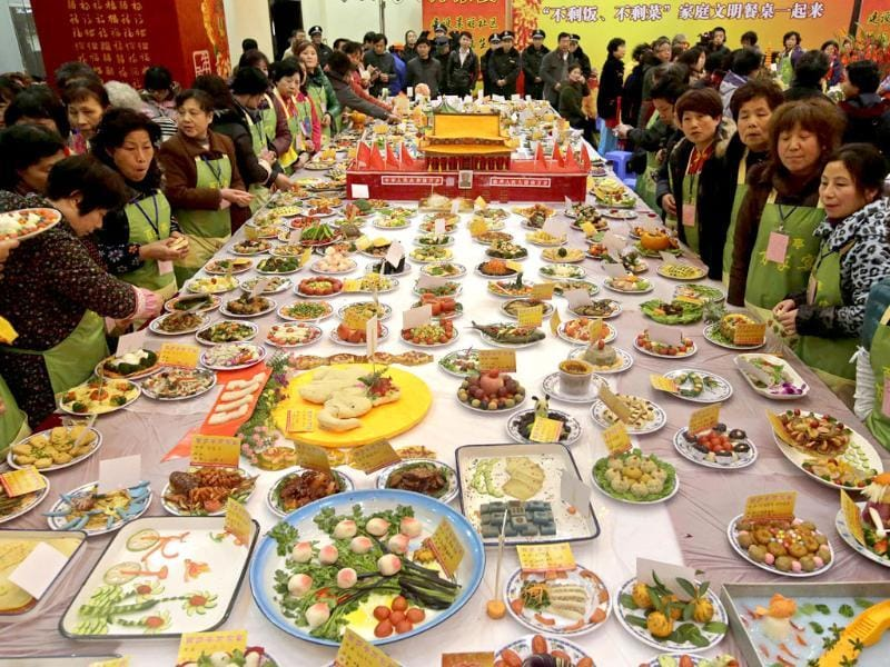 Neighbourhood residents stand around a table full of home-made dishes and a miniature replica decoration of the Tiananmen gate in the middle, during an annual local celebration for the upcoming Chinese New Year in Wuhan. Reuters/Darley Shen