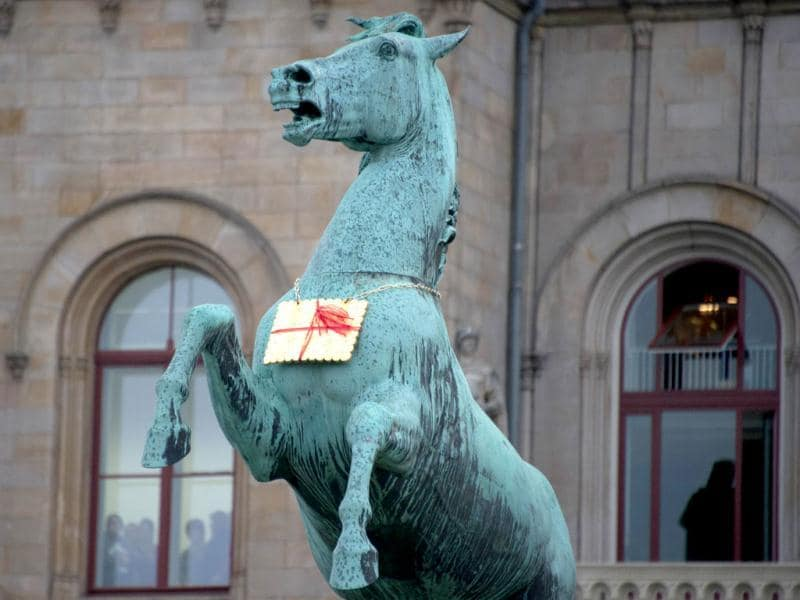 A golden Leibniz cookie hangs from a horses neck in front of the Leibniz University in Hannover, Germany. AP Photo