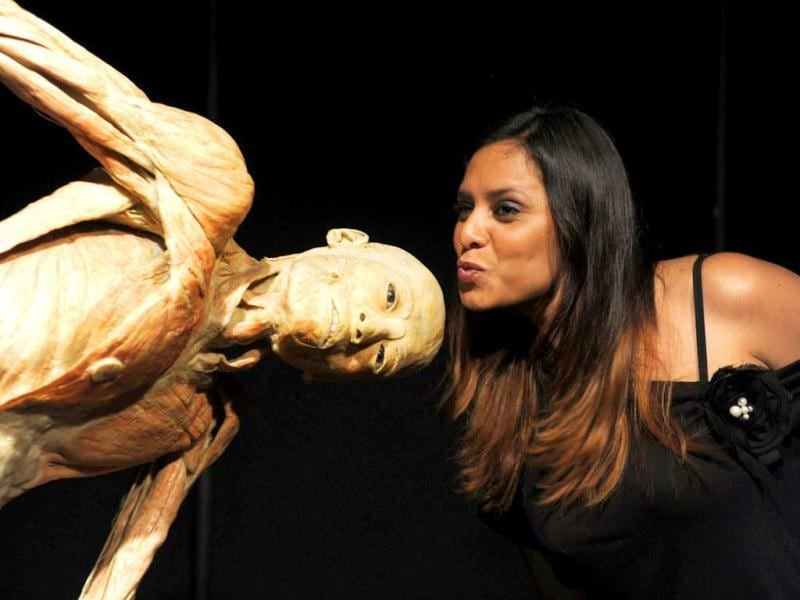A woman jokes next to a dissected and polymer-injected human body on display during the