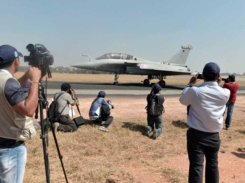 Photographers and video journalists record footage of a French Rafale fighter taxiing during Aero India 2013 at the Yelahanka Air Force station in Bangalore. AFP