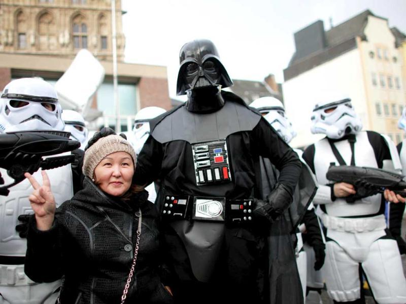 A woman poses with fools dressed as Darth Vader and star troopers during the beginning of the street carnival in Cologne, western Germany as the hot carnival season was launched. AFP Photo