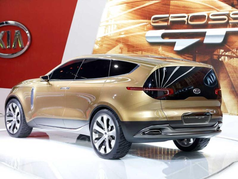 A visitor looks over cars in the Kia display during the media preview at the Chicago Auto Show in Chicago. (AFP Photo)