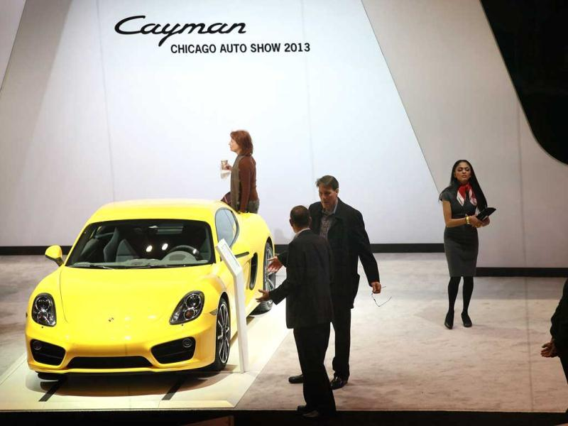 Visitors look over the Porsche Cayman during a media preview day at the Chicago Auto Show in Chicago. (AFP Photo)