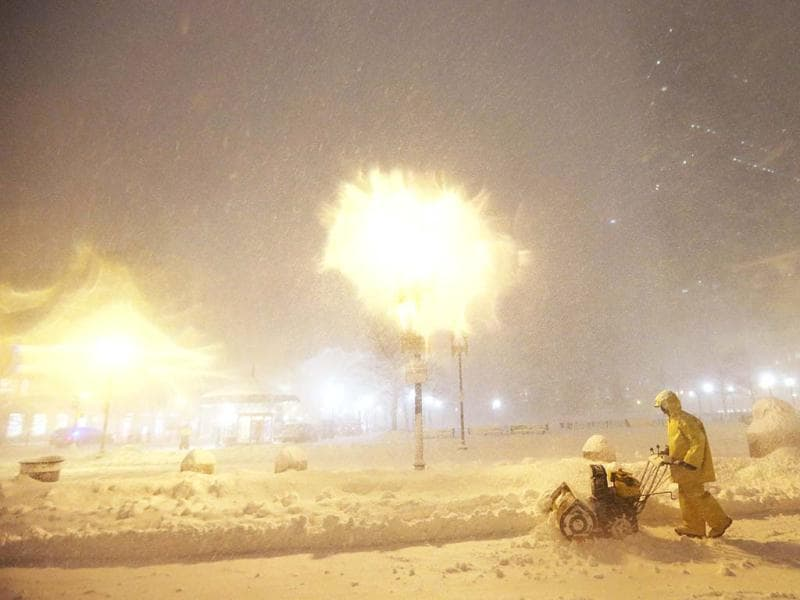 A man operates a snowblower while a blizzard arrives in the Back Bay neighborhood in Boston, Massachusetts. AFP