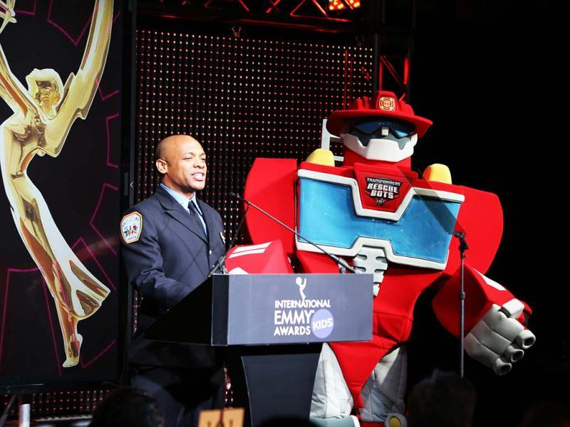 FDNY Firefighter Daniel Glover performs with Transformers Rescue Bot, Heatwave, during the International Emmy Kids Awards at Chelsea Piers in New York. (AP/International Academy of Arts and Sciences