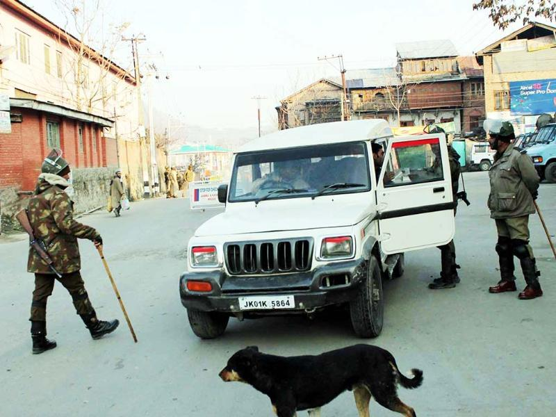 Security personnel check a vehicle in uptown Srinagar as authorities imposed curfew in all major parts of the Kashmir valley. UNI