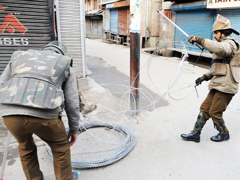 Policemen erect razor wire during a curfew in Srinagar. The curfew was imposed following the hanging of Parliament attack convict Afzal Guru. AFP/Rouf Bhat