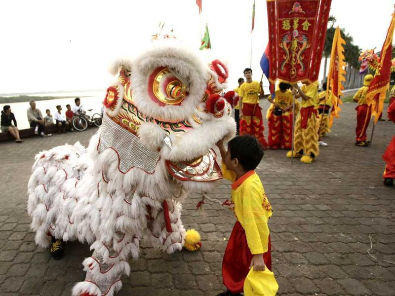 A boy touches a lion dancer as ethnic Cambodian Chinese community people perform a dragon dance in front of the Royal Palace ahead of Lunar New Year, in Phnom Penh, Cambodia. (AP Photo)