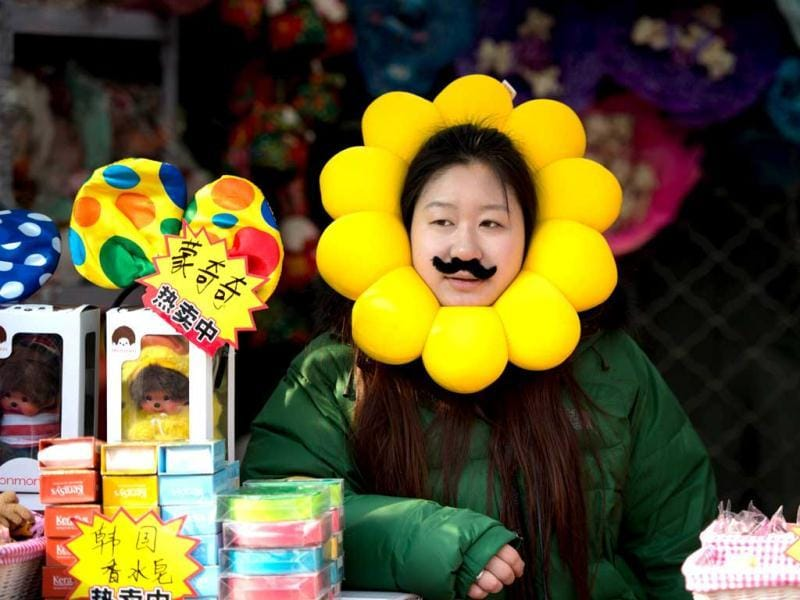 A vendor waits for customers in her stall at a temple fair in Ditan park in Beijing a day before the Lunar New Year. (AFP Photo)