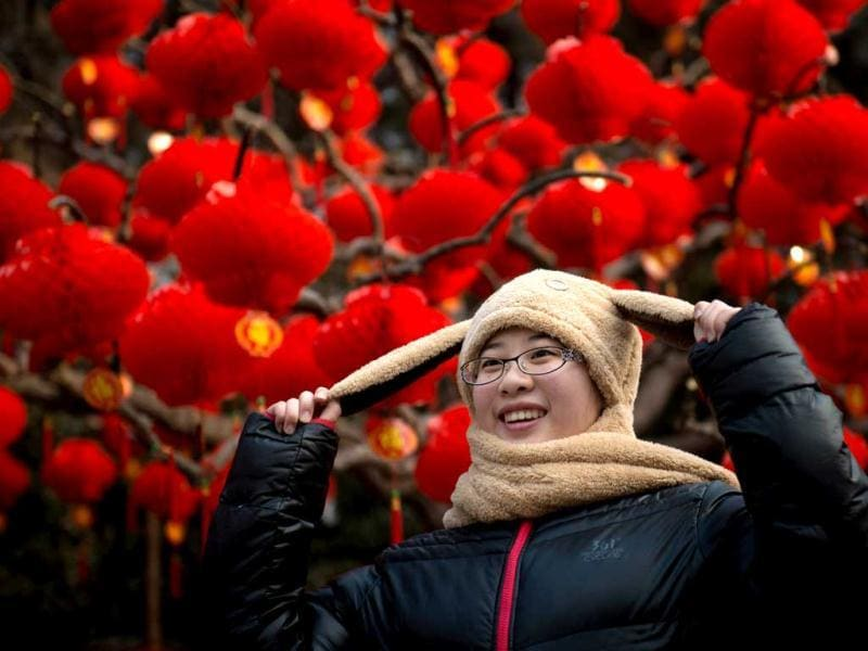 A woman poses before lanterns at a temple fair in Ditan park in Beijing a day before the Lunar New Year. (AFP Photo)
