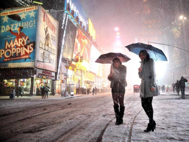 Two girls look for a taxi in the snow in Times Square in New York during a storm affecting the northeast US. AFP