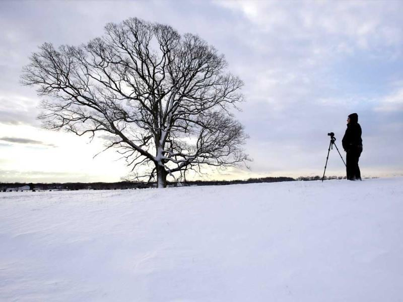 Sam Schepise braves the wind and cold to photograph the sunrise near Newtown, after a behemoth storm packing hurricane-force wind gusts and blizzard conditions swept through the Northeast. AP
