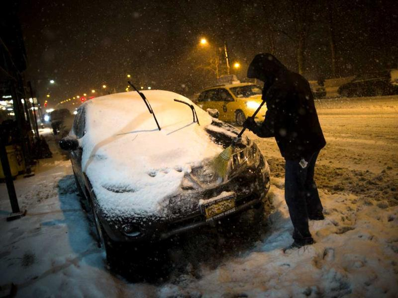 A motorist clears snow from his car on 59th Street in New York, as snow began falling across the Northeast. AP