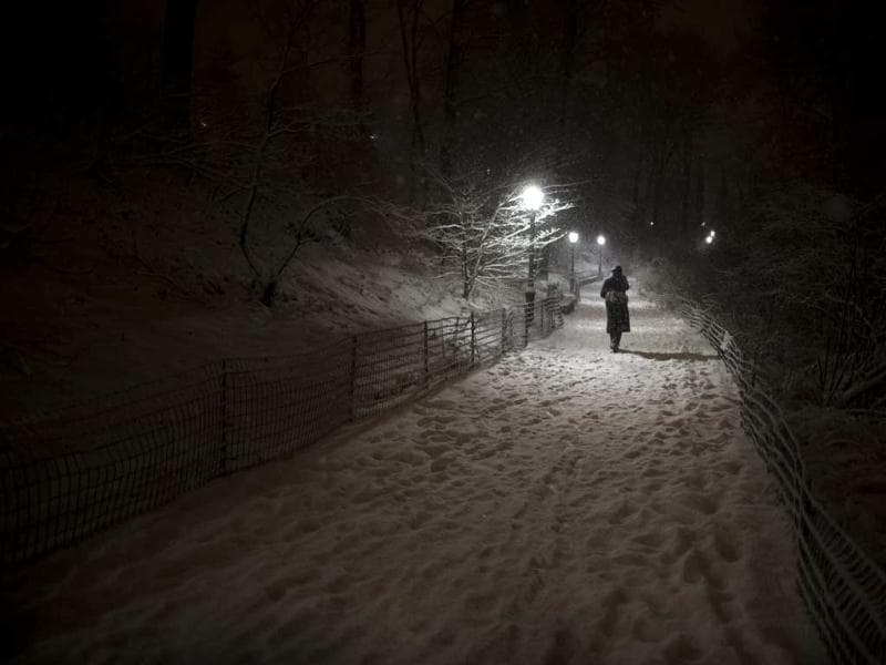 A pedestrian walks along a snowy path in Central Park in New York, after snow began falling across the Northeast. AP