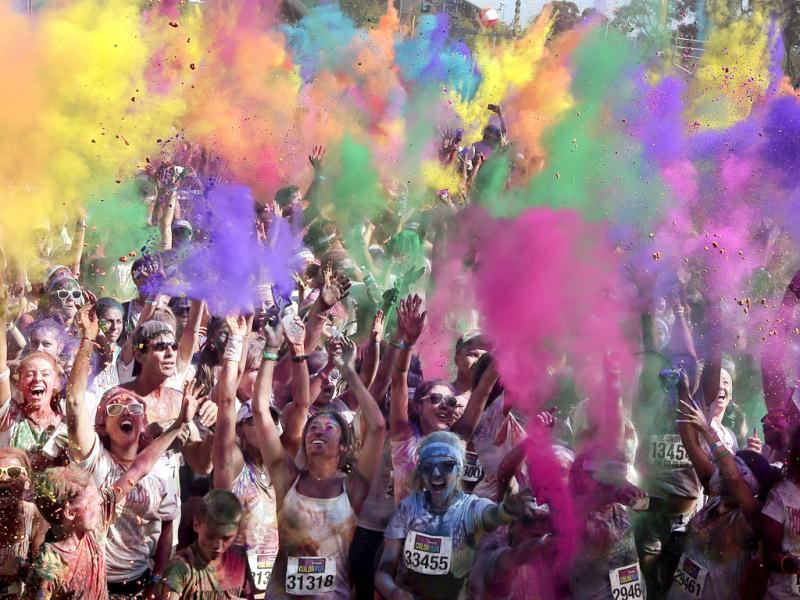 People celebrate in clouds of colored dust after the Swiss Color Run at Homebush Olympic Park in Sydney, Australia. AP