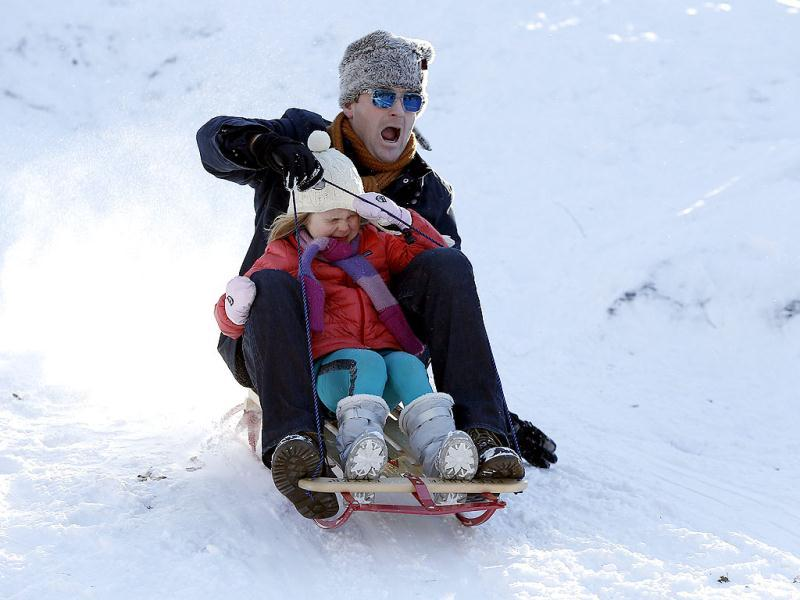 A man and child toboggan in Central Park in New York. A blizzard pummelled the Northeastern United States, killing at least one person, leaving hundreds of thousands without power and disrupting thousands of flights, media and officials said. Reuters