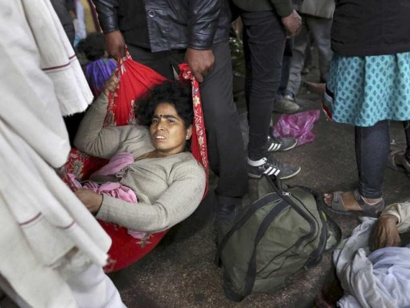 An injured woman who survived a stampede on a railway platform is carried away at the main railway station in Allahabad (AP Photo)
