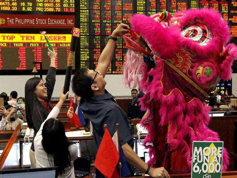 Traders offers a gift to a student wearing a traditional lion costume during Chinese New Year celebrations inside the trading floor of the Philippine Stock Exchange at financial district of Makati city, metro Manila. Reuters photo