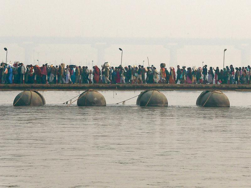 Hindu devotees walk across a pontoon bridge for a holy dip at Sangam, the confluence of the Ganges, the Yamuna and the Saraswati rivers, during the Maha Kumbh festival in Allahabad. The death toll from a stampede in a train station rose to 36 today. AP Photo