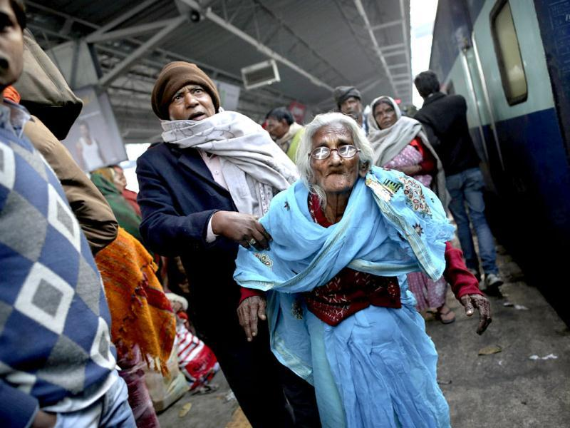 A woman is helped to her train on platform six near where a stampede took place a night before, at the station in Allahabad. AP photo