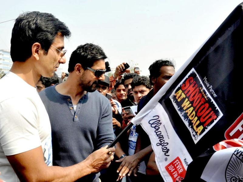John Abraham (2L) and Sonu Sood (L) pose at the Super Bike Rally for the promotion of Shoot out at Wadala in Mumbai on February 10, 2013. The movie is directed by Sanjay Gupta. (AFP PHOTO)