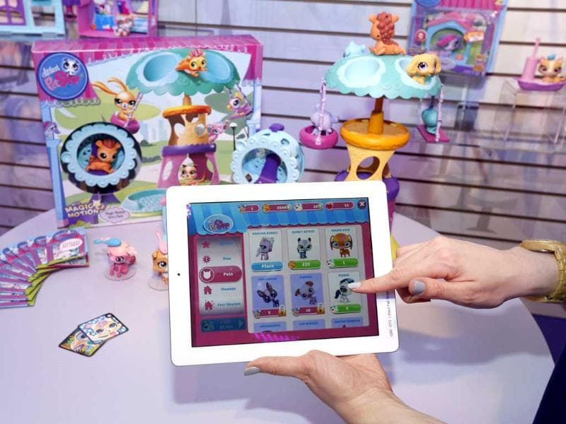 Demonstrator Chrysten Peddie plays the popular littlest pet shop app in Hasbro's showroom at the American International Toy Fair in New York. AP/Jason DeCrow/Invision for Hasbro