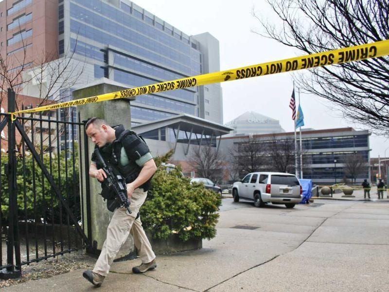 Law enforcement officials makes his way around the perimeter outside the New Castle County Courthouse in Wilmington, Delaware, after three people died on Monday morning in a shooting at a courthouse, including the shooter, authorities said. AP Photo